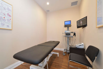A room with a physiotherapy bed and electronic equipment for assessment