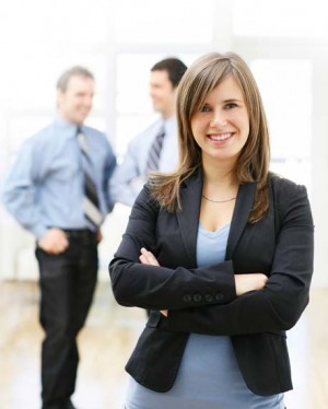 A corporate employee stands smiling at the camera with coworkers talking behind her