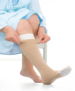 A patient putting compression stockings on their leg