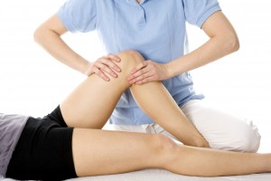 physiotherapist performing physiotherapy procedure on a patient's leg